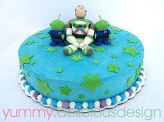 Pastel cubierto con betún de mantequilla y  figuras modeladas de fondant de Buzz lightyear y marcianitos...