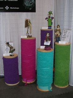 Pedestals - Sonotubes with wood tops and bottoms, painted and wrapped with thick yarn to look like spools of thread.  Brilliant idea for a sewing-related craft booth!  Full instructions here:  http://themagicbean.typepad.com/the_magic_bean/2012/04/going-once-going-twice-oversized-thread-spools-for-craft-fairs-exhibitions-or-shop-display-for-sale.html