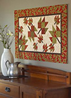 Autumn's olive, ecru, and cinnamon tones drift indoors in this striking wall quilt.