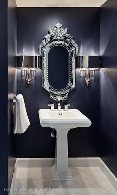 Chic blue bathroom with navy blue paint color, Global Views Hardwired Nickel Torch Sconces flanking Venetian mirror and white pedestal sink.