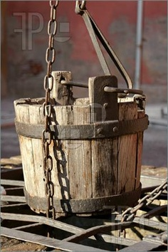 Image of Detail of an old well with wooden water bucket