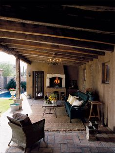 Mediterranean inspired backyard and covered patio / porch - Natural / Jute / Sisal rug - Fireplace - Stucco