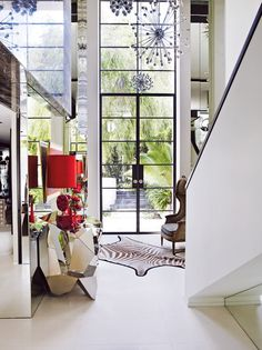 bold entry hall of Christian Lyon's Perth home with a mirrored angular console, red lamps, zebra-hide rug, balloon chair, and sputnik chandelier // foyers