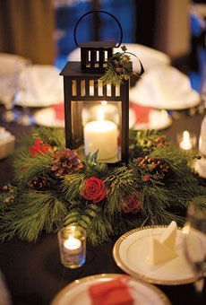 Lantern with white candle centered in evergreen wreath with pine cones and flowers or berries.