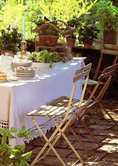 like the lace table cloth, birdcage, lantern plants, antiqued chairs and everything.  just waiting for summer!