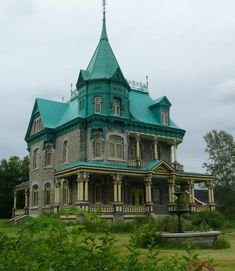 Victorian House with Gray stone. Wrap-around porch. Huge windows.  Victorian, Gothic ironwork. A turret. Fountain in the yard.