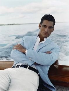 David Gandy relaxing in dark stained wood boat, white shirt with standup collar, open at the neck, white pants, black belt, light blue jacket