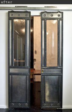 Antique elevator doors repurposed as sliding doors.