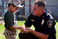 Jorge Solis, 5, shows Marine Corps Sgt. Benjamin Maple the challenge coins he recieved during his tour of Marine Corps Base Camp Pendleton, Calif., Aug. 10, 2012.    Solis, who has retinoblastoma, a rare eye cancer, wished to be a Marine for a day. Maple is kennel master at the K-9 kennels on the Marine base.     U. S. Marine Corps photo by Cpl. Jovane Henry