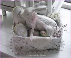 A white Easter basket I made for my mom last year with a white cast bunny a vintage German lamb and embellished paper maché eggs.