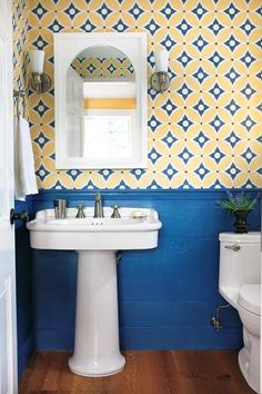 If you normally shy away from patterns, try one on for size above wainscot in a powder room. Here, hand-painted canvas that matches the house's colonial history features a vibrant pattern that perks up the space. | Photo: Keller & Keller