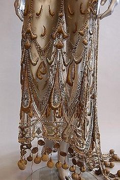 An embroidered gold tulle tabard, circa 1910-12, worked in raised silver and gold threads, blue floss silks in grand belle epoque style, the trained hem adorned with gold thread rouleaux and padded pom-poms. Detail front