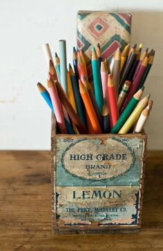 Great desk organization: colored pencils in a vintage wooden crate.