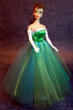 Vintage Barbie Senior Prom      Vintage Barbie Senior Prom #951 (1963-1964)    Green Satin Gown  Green Open Toe Heels with Pearls    This is Barbie's glamorous strapless prom gown, and a favorite of vintage collectors.      The gown is emerald green satin with blue satin around the top of the bodice and green and blue tulle overskirt.  The shoes are emerald green open toe heels with pearl accents.