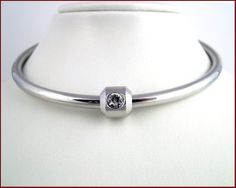 Rolled steel collar w/ swarovski crystal pendant that locks on with a key.  Lovely.  €120