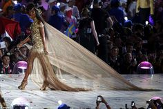 Shimmering: Naomi Campbell, draped in gold, takes over, strutting in a dazzling gold McQueen dress with a long train