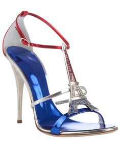 Metallic leather 'Tour Eiffel' sandals from Giuseppe Zanotti, featuring a blue strap across the toe, a silver strap across the foot, a thin adjustable red ankle strap with a silver buckle and a silver Eiffel Tower with crystal embellishment on the T-bar. These sandals have a metallic blue insole with a silver trim and a high silver stiletto heel.