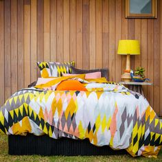 Love the bedding and the pop of yellow against the wood panel