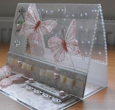 handmade card ... easel card design ... clear acetate top ... adorned with ribbon, pearls. silver stickers ... gorgeous feathery butterflies .... pink and gray ... luv it!!