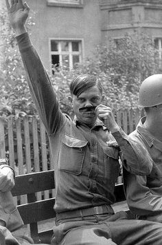 A U.S. soldier mocks Hitler for the camera, World War II.