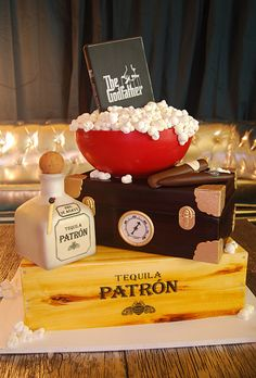 Brides.com: Unique Groom's Cakes. An edible representation of the groom's favorite things: The Godfather films (the DVD is actually a solid piece of chocolate), good tequila (the bottle of Patrón is made of Rice Krispies Treats), and cigars (the humidor is handpainted to resemble wood and decorated with gold gumpaste hardware).  Cake design by Gateaux Inc. cake wedding, tequila, the godfather, brides, rice krispies treats, wedding cakes, groom cake, cake designs, grooms