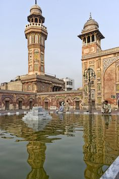 Wazir Khan Mosque is located near the Delhi Gate within the ancient Walled City of Lahore, Pakistan. The minaret reflects in the pool located in the central courtyard of the mosque. by Ali Khan