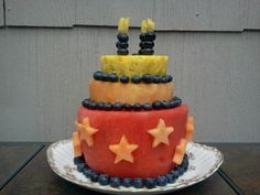My version of a fresh fruit birthday 'cake' for my boy who won't eat traditional cakes.   -  To keep tiers from sliding I made a shallow hollow with Mellon-baller for each tier to sit in. I used cookie cutters and cut out stars with cantaloupe,  and his name with pineapple.  His name is pinned on with toothpicks on the watermelon layer on the front of the cake, not in this photo. I also put his age, in pineapple on the middle layer.and a star in cantaloupe,  on the top pineapple layer. He loved it.