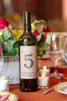 We LOVE these wine bottle table numbers. Photo by Jeannine. #WeddingPlannersMN #WeddingTableNumbers