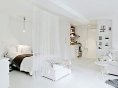 A sheer curtain at the foot of the bed to define the bedroom area in a studio apartment.