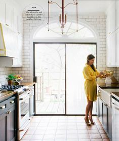 kitchen with dark cabinets, white subway lined walls with dark grout, oversized lantern