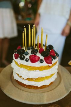 cake topped with fruit + gold candles // photo by Jill DeVries // http://ruffledblog.com/whimsical-michigan-wedding