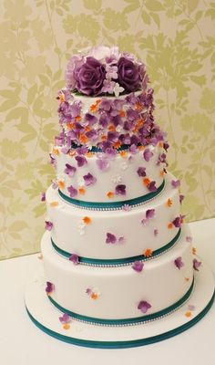 Purple and orange Cascading hydrangea and blossom wedding cake with a rose topper
