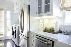 Stunning galley kitchen design with white glass-front kitchen cabinets with marble countertops, farmhouse sink, subway tiles backsplash, white front-load washer & dryer in kitchen and yellow & gray roman shade