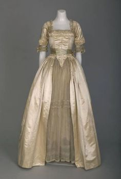 """Wedding Dress, Lucile, Chicago: 1916, silk satin, Valenciennes and Chantilly lace, silk flowers, petticoat of """"Pussy Willow"""" silk. """"Worn by Katherine Keith at her marriage to David Adler on June 1, 1916. This wedding dress shows direct reference to a style of dress popular in the mid-to-late eighteenth century that had a wide skirt supported by a boned understructure called a pannier...The pannier in this dress is one single piece of boning stitched into the lining of the garment."""""""