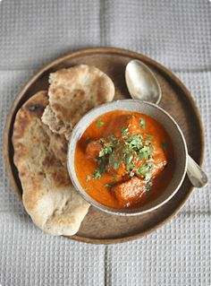 Butter Chicken - One of the Best Indian Food Dishes with a hunk of naan bread on the side that is bread dough cooked inside a flower pot style tandori oven. It tastes like tomato soup with chunks of flavorful chicken.