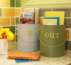 Recycle Those Paint Cans  Create a spot to drop incoming and outgoing mail with this clever project. Remove the handles of paint cans and paint the buckets to match your room. Add words using stickers from the scrapbooking store, and then reattach the handles. Set the cans near the front door or at a kitchen workstation.
