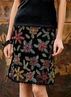 Colorful crochet motifs grounded in black crocheted mesh