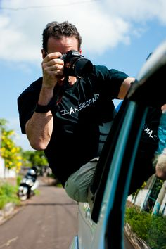 Pat Davison takes photos of students while hanging from the back of a speeding taxi on the way to Playa Mann and GAIAS on the Galapagos Islands. Carolyn Van/reesenews