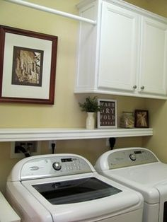 I like this narrow shelf over the washer and dryer to hide the fact that they can't be pushed back all the way against the wall.  Also like cabinets above.