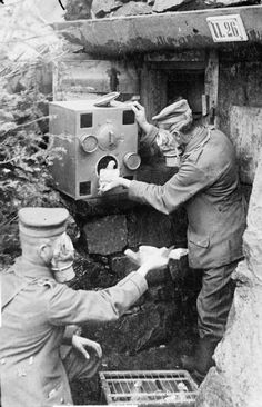 German soldiers wear respirators as they place carrier pigeons into a gas-proof chamber, presumably during an anti-gas drill.