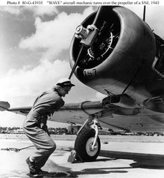 WAVES aircraft mechanic turns over the propeller of a SNJ.