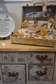 Old suitcase used as display for old family photos...love the seashells mix...