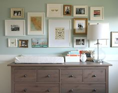 source: Our House    Gorgeous eclectic nursery with Ikea Hemnes 8-Drawer Dresser in gray-brown as changing table. The dresser is topped with a glass lamp, gold photo frame and white owl. Above the dresser hangs an eclectic art collection with prints, photos and paintings. The lower nursery walls are painted white with a mint green upper wall.