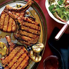 Grilled Pork Chops with Apple-Bourbon Glaze |  The key to success here is to brush the Apple-Bourbon Glaze on the chops during the last few minutes on the grill, turning and brushing often to create a layered, lacquered look. Garnish the chops with grilled halves of small apples brushed with the glaze.