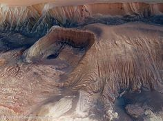 Collapse in Hebes Chasma on Mars. The above image, taken by the robotic Mars Express spacecraft currently orbiting Mars, shows great details of the chasm and the unusual horseshoe shaped indentation in the central mesa. Material from the mesa appears to have flowed onto the floor of the chasm, while a possible dark layer appears to have pooled like ink on a downslope landing.