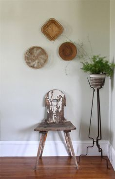 white chair with baskets on wall