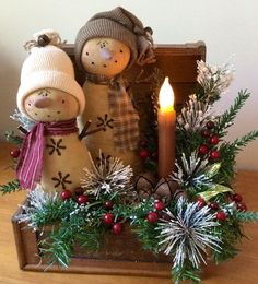 Vintage chest with two prim snow folk .......this chest is embellished with pine, frosted Ming, lacquered berries, assorted rusty jingle bells, glittery leaves and a battery operated, wax dipped flicker candle.   $38