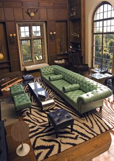 Living Room - Beautiful architectural elements wrapped in wood paneling.  The customized long mint green leather tufted sofa is impressive as is the zebra design area rug anchoring the stage for seating.  Style juxtapositions that are highly original & cleverly conceived in evocative combinations.