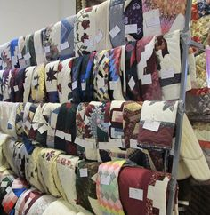 Amish Mud Sale in Lancaster County Pa.    This photo shows some of the handmade Amish quilts that will be auctioned off. They are placed on racks and numbered. The bidders have enough time before the auction to walk around and jot down the numbers of the quilts they wish to buy.
