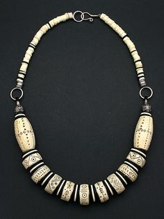Necklace | Dorothy Siemens | Faux bone (Polymer clay) effects over sewing machine bobbins.